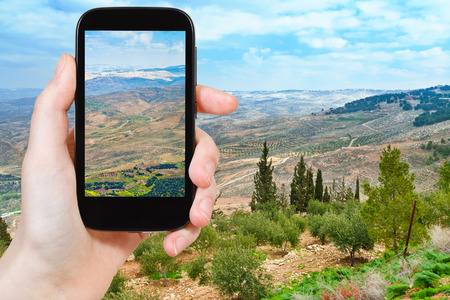 promised: travel concept - tourist taking photo of Promised Land from Mount Nebo in Jordan on mobile gadget