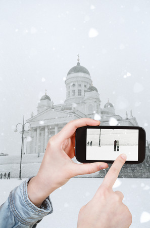 travel concept - tourist taking photo of Helsinki Cathedral in winter on mobile gadget, Finland photo