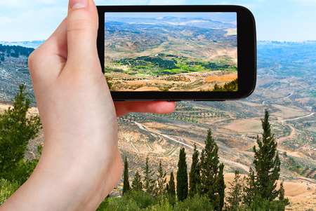 holy land: travel concept - tourist taking photo of Holy Land from Mount Nebo in Jordan on mobile gadget Stock Photo