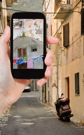 felice: travel concept - tourist taking photo of small side street in italian town San Felice Circeo on mobile gadget, Italy