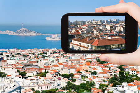 chateau d if: travel concept - tourist taking photo of Marseille city skyline on mobile gadget, France
