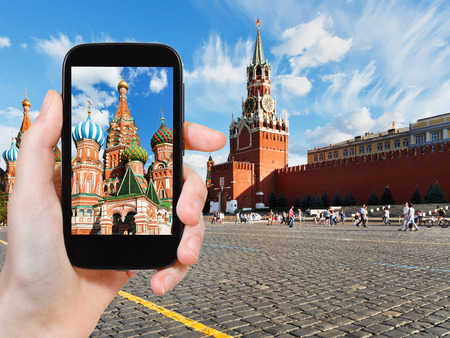 travel concept - tourist taking photo of Red Square in Moscow in summer day on mobile gadget, Russia photo
