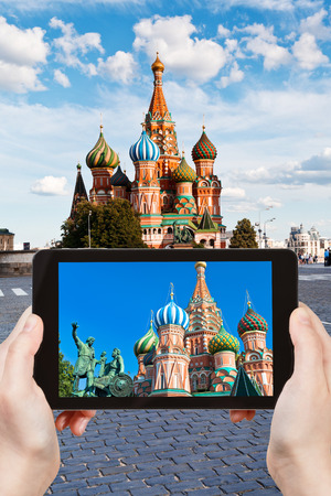 pokrovsky: travel concept - tourist taking photo of Pokrovsky cathedral on Red square in Moscow on mobile gadget, Russia Stock Photo