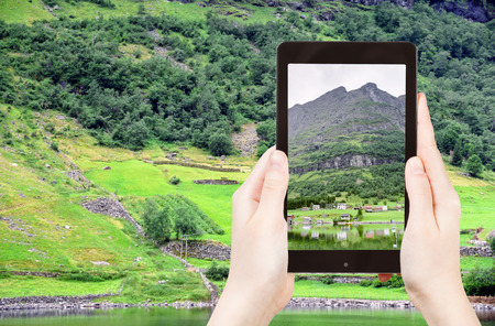 fiord: travel concept - tourist taking photo of village in Norway on coast of fiord on mobile gadget