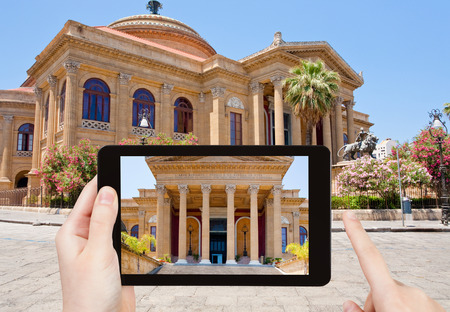 massimo: travel concept - tourist taking photo of Teatro Massimo - famous opera house in Palermo, Sicily on mobile gadget, Italy
