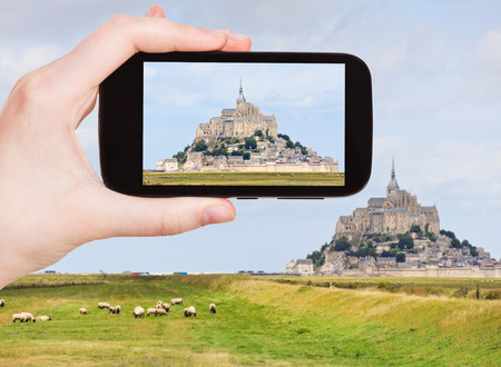 mount saint michael: travel concept - tourist taking photo of mont saint-michel abbey, Normandy in summer, France on mobile gadget