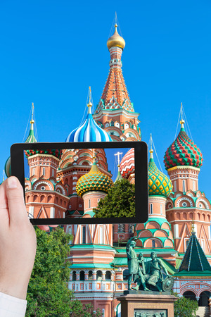 minin: travel concept - tourist taking photo of colors towers of Saint Basil cathedral on Red Square in Moscow on mobile gadget, Russia Stock Photo