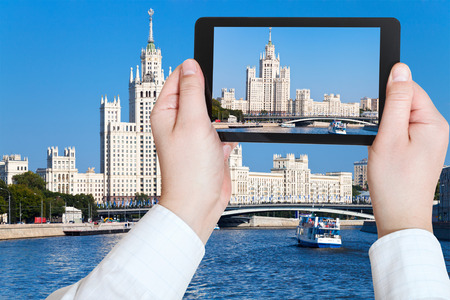 kotelnicheskaya embankment: travel concept - tourist taking photo of Moscow cityscape with Stalins high-rise building on kotelnicheskaya embankment on mobile gadget, Russia Stock Photo