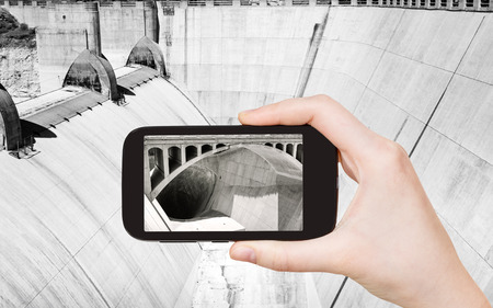 hoover: travel concept - tourist taking photo of Hoover Dam on mobile gadget, USA