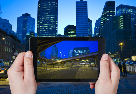city landscape: travel concept - tourist taking photo of New York City in night on mobile gadget
