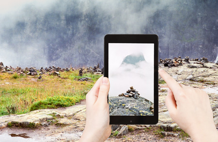 pyramid peak: travel concept - tourist taking photo of stone pyramid on mountain plateau in Norway on mobile gadget