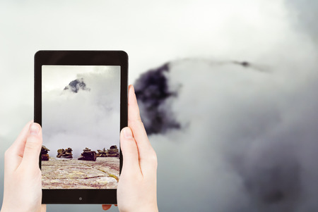 pyramid peak: travel concept - tourist taking photo of stone pyramid on mountain plateau in Norway with mountain peak and cloud on background on mobile gadget