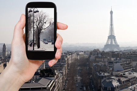 d'eiffel: travel concept - tourist taking photo of Avenues in Paris in early spring on mobile gadget, France Stock Photo