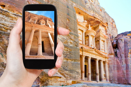 treasury: travel concept - tourist taking photo of Treasury Monument temple in rock in ancient city Petra on mobile gadget, Jordan
