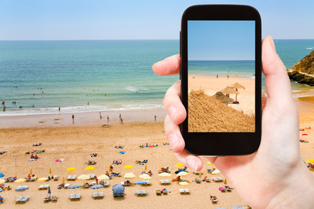 landscape scene: travel concept - tourist taking photo of Atlantic beach in Algarve, Portugal on mobile gadget