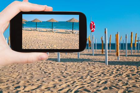 beach scene: travel concept - tourist taking photo of straw beach umbrellas on ocean coast, Portugal, Algarve on mobile gadget Stock Photo