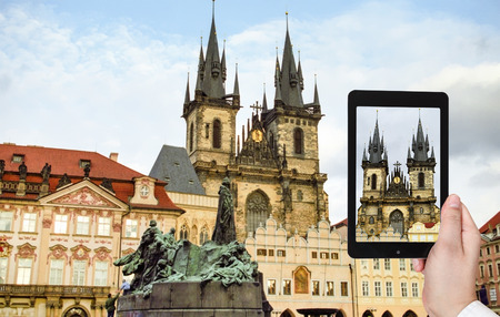travel concept - tourist taking photo of Church of Our Lady before Tyn in Prague on mobile gadget, Czech photo