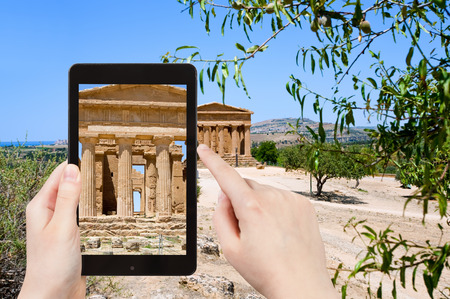 valley of the temples: travel concept - tourist taking photo of ancient Temple of Concordia in Valley of the Temples, Agrigento, Sicilyon mobile gadget