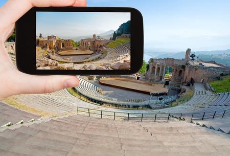 amphitheatre: travel concept - tourist taking photo of ancient amphitheater Teatro Greco, Taormina, Sicily on mobile gadget, Italy