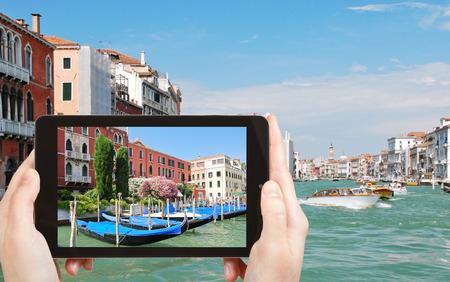 travel concept - tourist taking photo of parking of gondolas near Ponte di Rialto in Venice, Italy on mobile gadget photo