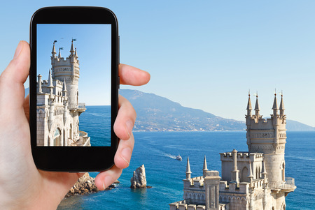 travel concept - tourist taking photo of Swallows Nest palace on Southern Coast of Crimea on mobile gadget photo