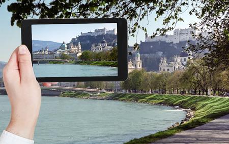 salzach: travel concept - tourist taking photo of Salzach River and Salzburg city on mobile gadget, Austria