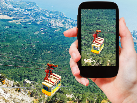 travel concept - tourist taking photo of Cableway Miskhor - Ai-Petri over Crimean mountains on mobile gadget, Crimea photo