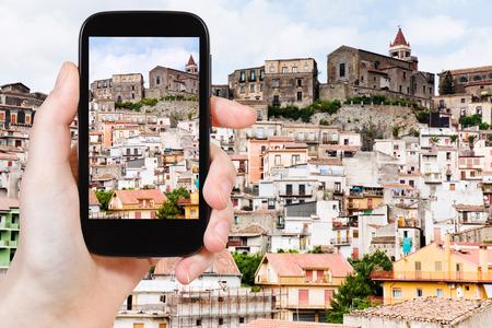 sicilia: travel concept - tourist taking photo of small sicilian mountain town Castiglione di Sicilia on mobile gadget, Italy