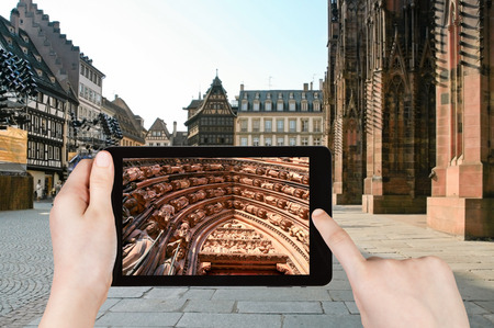 fragments: travel concept - tourist taking photo of cathedral in Strasbourg, France on mobile gadget