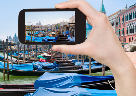 piazza san marco: travel concept - tourist taking photo of gondolas near Piazza San Marco in Venice, Italy on mobile gadget