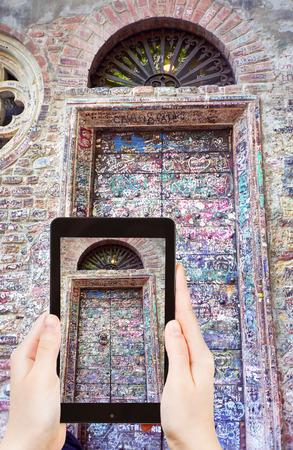 juliets: travel concept - tourist taking photo of door of Juliet House (Casa di Giulietta) in Verona on mobile gadget, Italy