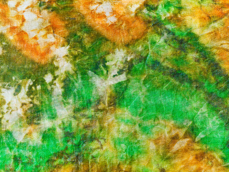 abstract ornament of green yellow batik painted on silk close up photo