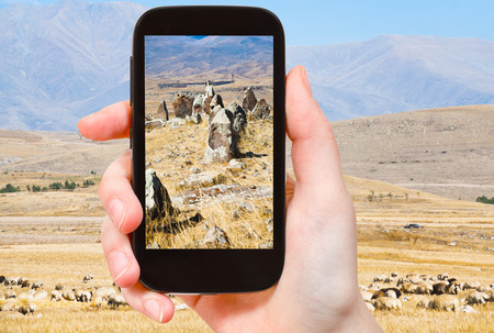 prehistory: travel concept - tourist takes picture of standing menhirs of Zorats Karer (Carahunge) - pre-history megalithic monument in Armenia on smartphone,