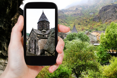 geghard: travel concept - tourist takes picture of Katoghiken church of medieval geghard monastery in Armenia on smartphone, Stock Photo