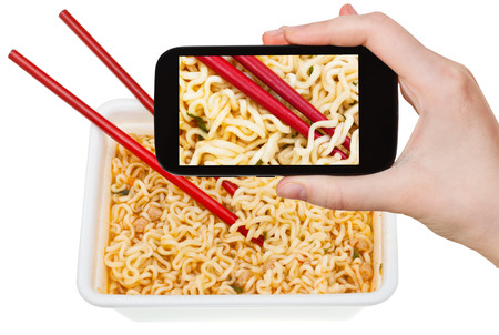 instant ramen: photographing food concept - tourist takes picture of red chopsticks on chinese cooked instant ramen on smartphone, Korea Stock Photo