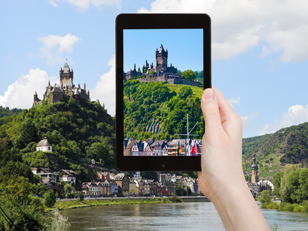 mosel: travel concept - tourist takes picture of view of Cochem town on Moselle river and Cochem Imperial castle over town in Germany on smartphone, Editorial