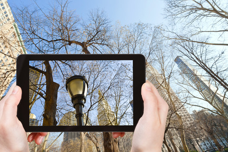 travel concept - tourist takes picture of houses and bare trees in New York in autumn on smartphone, photo