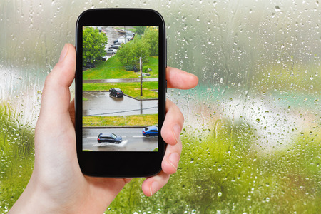 soppy: travel concept - tourist takes picture of shower in city from home window on smartphone,