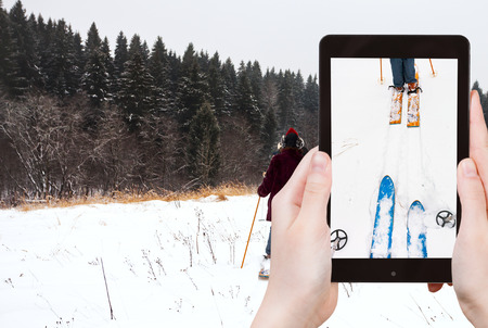 ski run: travel concept - tourist takes picture of wide cross-country skis and ski run in snow on smartphone,