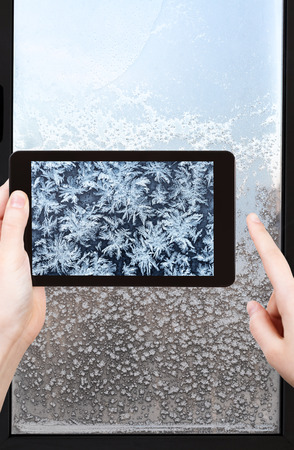 window pane: travel concept - tourist takes picture of snowflakes and frost pattern on window pane in cold winter evening on smartphone,