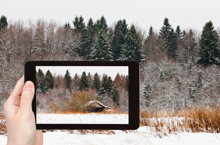 snowed: travel concept - tourist takes picture of low wooden house on edge of snowed forest in cold winter day on smartphone, Stock Photo