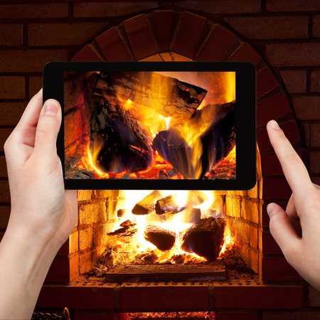 stone fireplace: travel concept - tourist takes picture of burning wood in fireplace in evening time on smartphone,