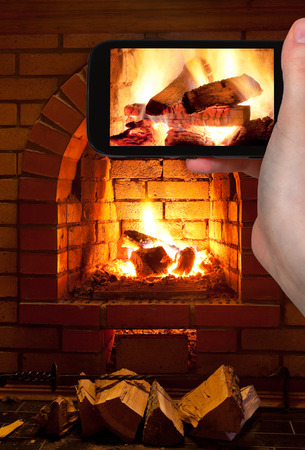 firebox: travel concept - tourist takes picture of burning wood in fireplace in evening time on smartphone,