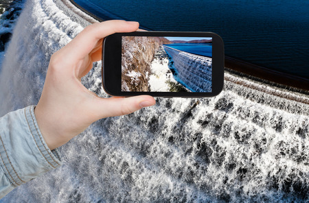 travel concept - tourist takes picture of river waterfall on Croton Dam in winter day on smartphone, USA photo