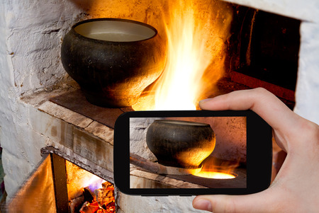 culinary tourism: photographing food concept - tourist takes picture of fire hearth of russian stove and old cast iron pot with oven fork on smartphone,