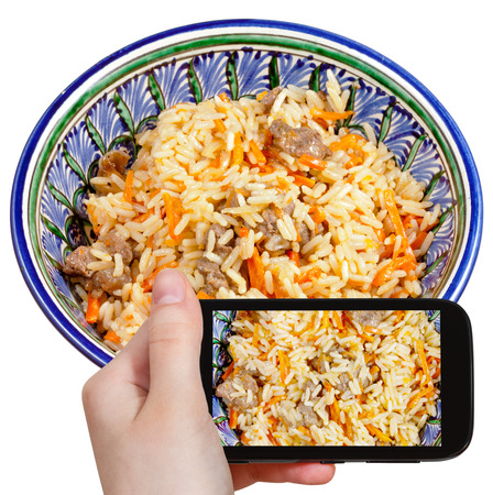culinary tourism: photographing food concept - tourist takes picture of traditional asian pilau with meat in ceramic bowl on smartphone, Uzbekistan