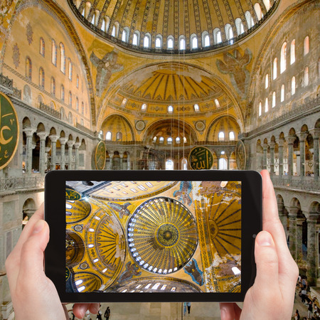 sightseeng: travel concept - tourist takes picture of interior and cupola on Hagia Sophia, Istanbul, Turkey on smartphone,