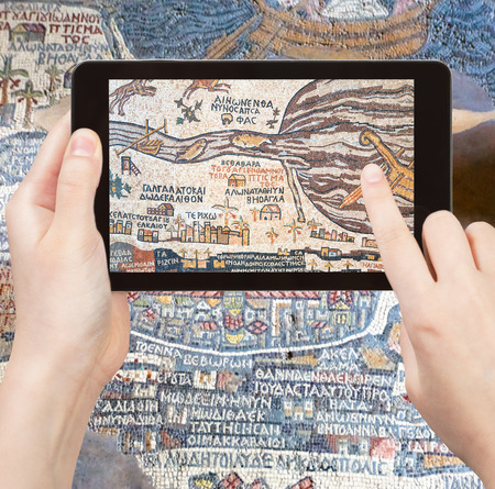 holy land: travel concept - tourist takes picture of ancient byzantine map of Holy Land, Madaba on smartphone, Jordan