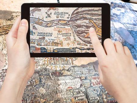 the holy land: travel concept - tourist shoots photo of ancient byzantine map of Holy Land, Madaba on smartphone, Jordan Stock Photo