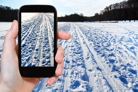 ski runs: travel concept - tourist takes picture of ski runs in snowy field in cold winter day on smartphone,